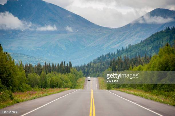 Single car with camper driving on Parks Highway in Alaska