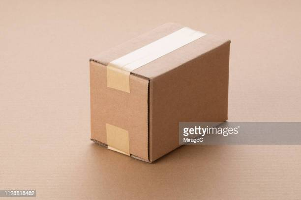 single cardboard box on brown paper - cardboard box stock pictures, royalty-free photos & images