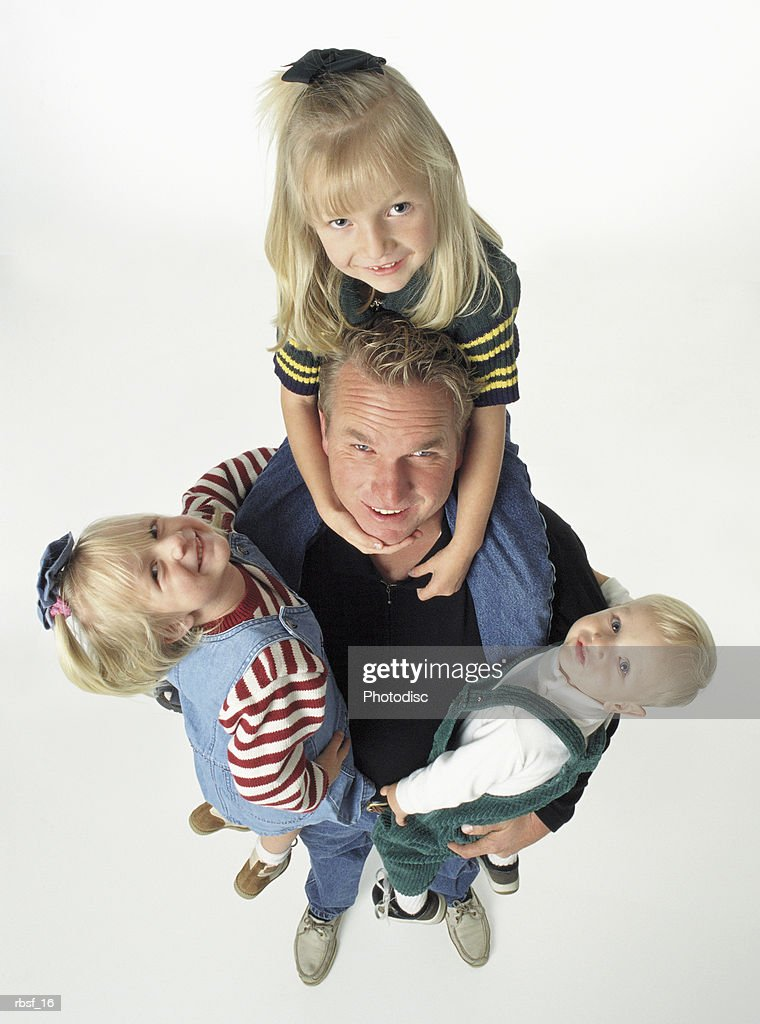 single caucasian father with three blonde kids holds two in his arms with one riding on his shoulders : Foto de stock