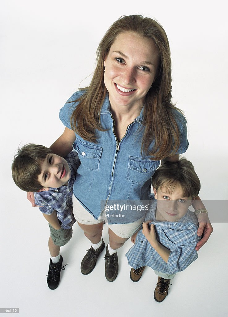 single caucasian mom with brown hair in shorts and denim shirt stands between two young kids : Foto de stock