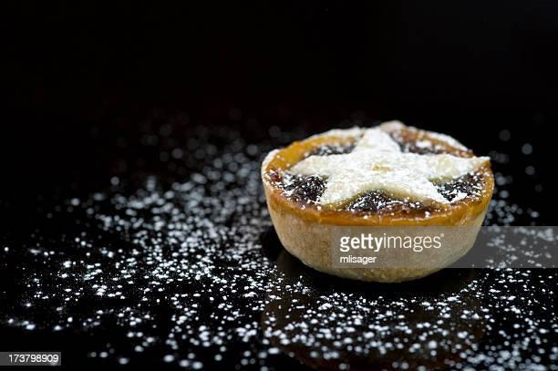 Single Christmas mince pie on black background