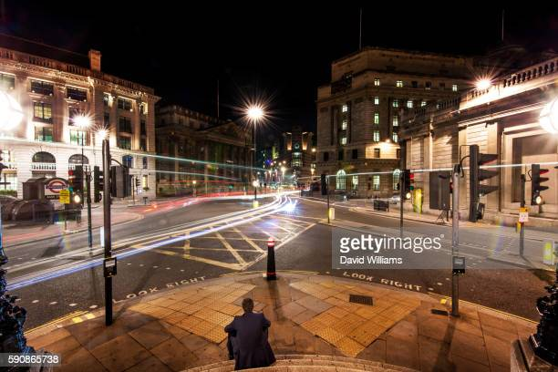 A single City worker sits on the steps of Bank Junction, City of London