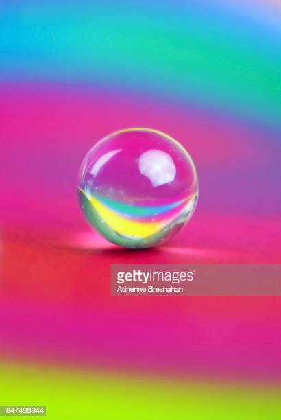 Single Clear Marble on a Rainbow-Colored Background