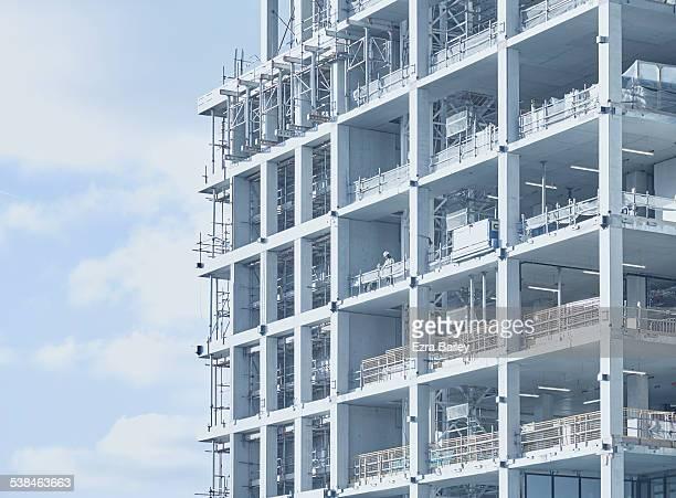 a single construction worker on a building site. - built structure - fotografias e filmes do acervo