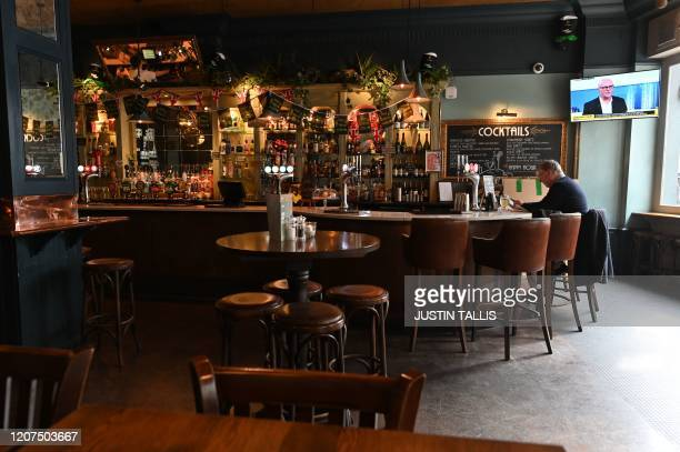 Single customer sits at the bar in a near-empty pub in central London on March 17, 2020 after the UK government announced stringent social distancing...