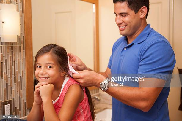 Single dad adds a bow to daughter's hair in bathroom.