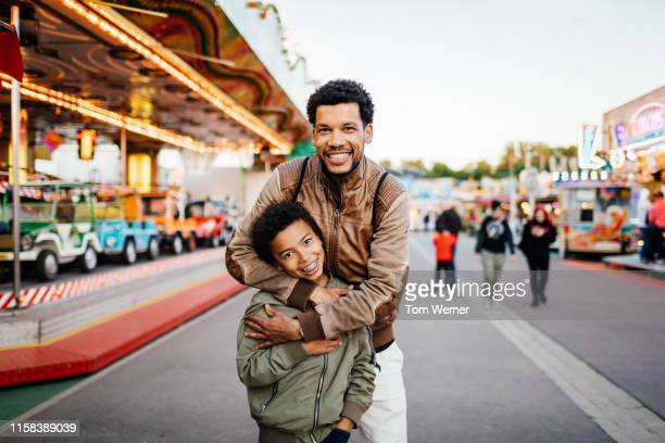 single dad affectionately embracing son at fun fair - one parent stock pictures, royalty-free photos & images