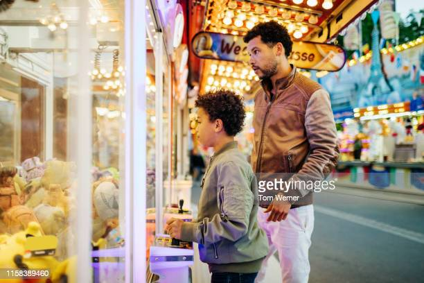Single Dad Playing Claw Machines With Son At Fun Fair