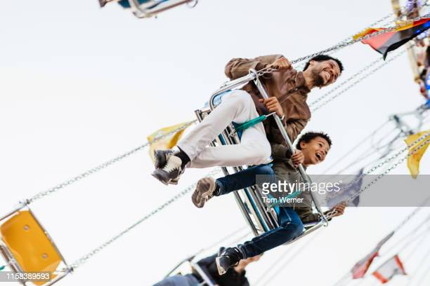 single dad riding swings at fun fair with son - amusement park ride stock pictures, royalty-free photos & images