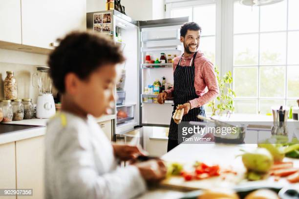 single dad smiling while he prepares lunch for son at home - haushaltsmaschine stock-fotos und bilder