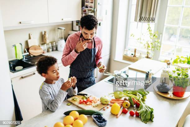 single dad snacking with his son while preparing lunch - gezonde voeding stockfoto's en -beelden