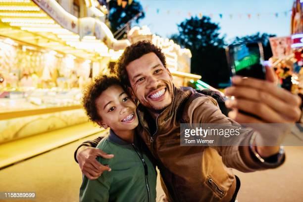 single dad taking selfie with son at the fun fair - レザージャケット ストックフォトと画像
