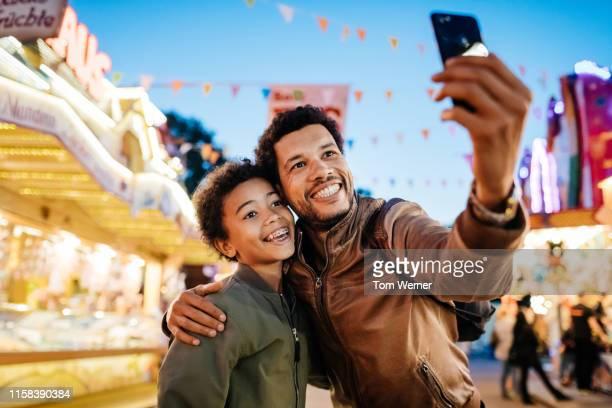 single dad with son taking selfie at the fair - carnaval evento de celebración fotografías e imágenes de stock