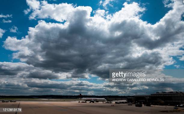 A single Delta airlines plane is seen next to empty gates at Ronald Reagan Washington National Airport in Arlington Virginia on May 12 2020 The...