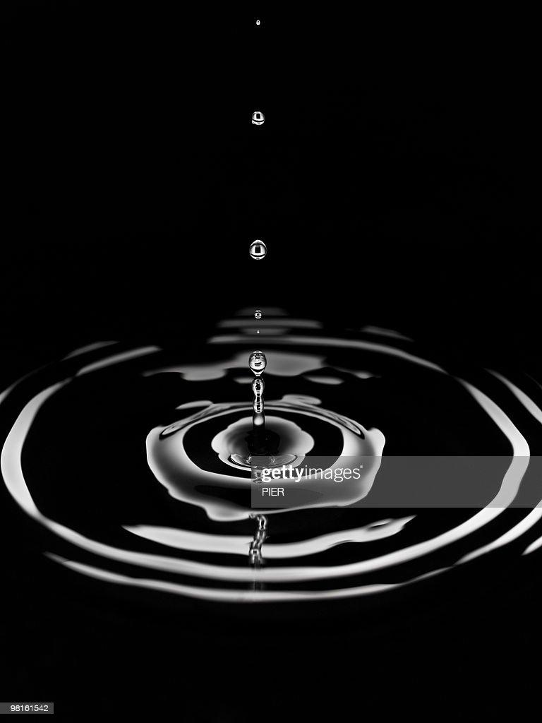 Single drop of water forming rings in pool : Stock Photo