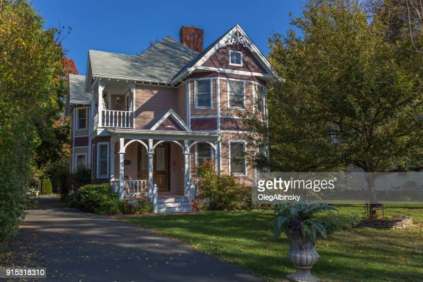 Single Family Home with Beige and Brown Clapboard Exterior and Trees in Autumn Colors (Foliage) in Rhinebeck, Hudson Valley, New York.