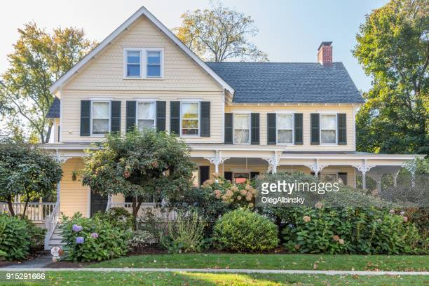Single Family Home with Beige Clapboard Exterior and Trees in Autumn Colors (Foliage) in Rhinebeck, Hudson Valley, New York.