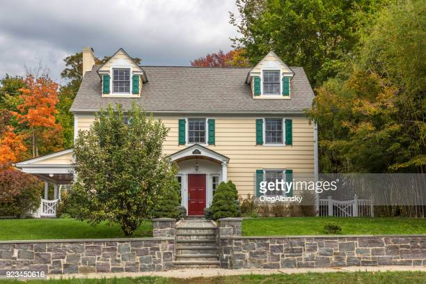single family home with beige clapboard exterior and trees in autumn colors (foliage) in sleepy hollow, hudson valley, new york. - westchester county stock pictures, royalty-free photos & images