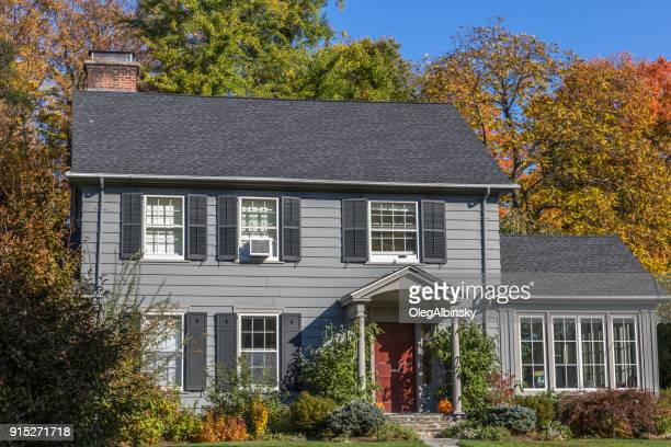 Single Family Home with Gray Clapboard Exterior and Trees in Autumn Colors (Foliage) in Rhinebeck, Hudson Valley, New York.
