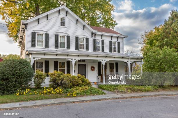 Single Family Home with White Clapboard Exterior and Trees in Autumn Colors (Foliage) in New Paltz, Hudson Valley, New York.