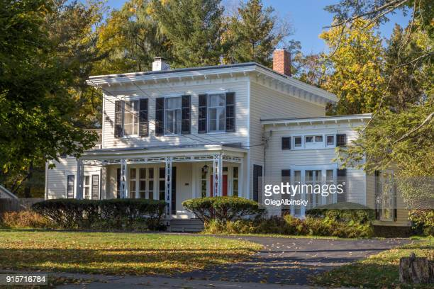 Single Family Home with White Clapboard Exterior and Trees in Autumn Colors (Foliage) in Rhinebeck, Hudson Valley, New York.