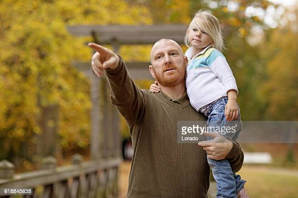 Single father and blonde daughter posing in autumnal park surroundings