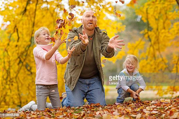 Single father and daughters playing together in autumnal park surroundings