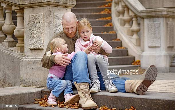 Single father and daughters sitting together on stately autumnal steps