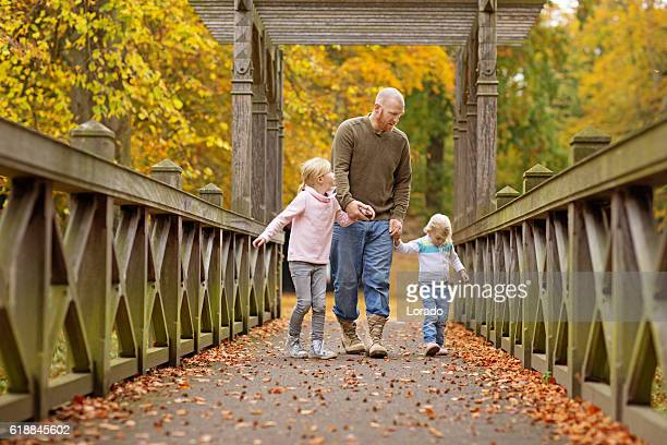 Single father and daughters walking together in autumnal park surroundings