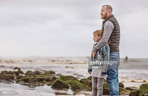 single father and his daughter playing family games on a winter beach - mourning stock pictures, royalty-free photos & images