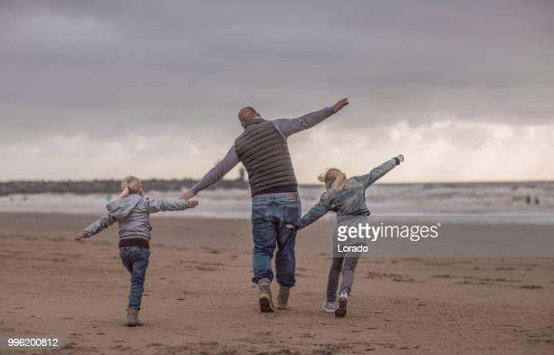 alleenstaande vader en zijn dochters familie spelen op een winter-strand - nederlandse cultuur stockfoto's en -beelden