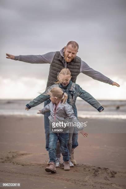 alleenstaande vader en zijn dochters familie spelen op een winter-strand - menselijke relaties stockfoto's en -beelden