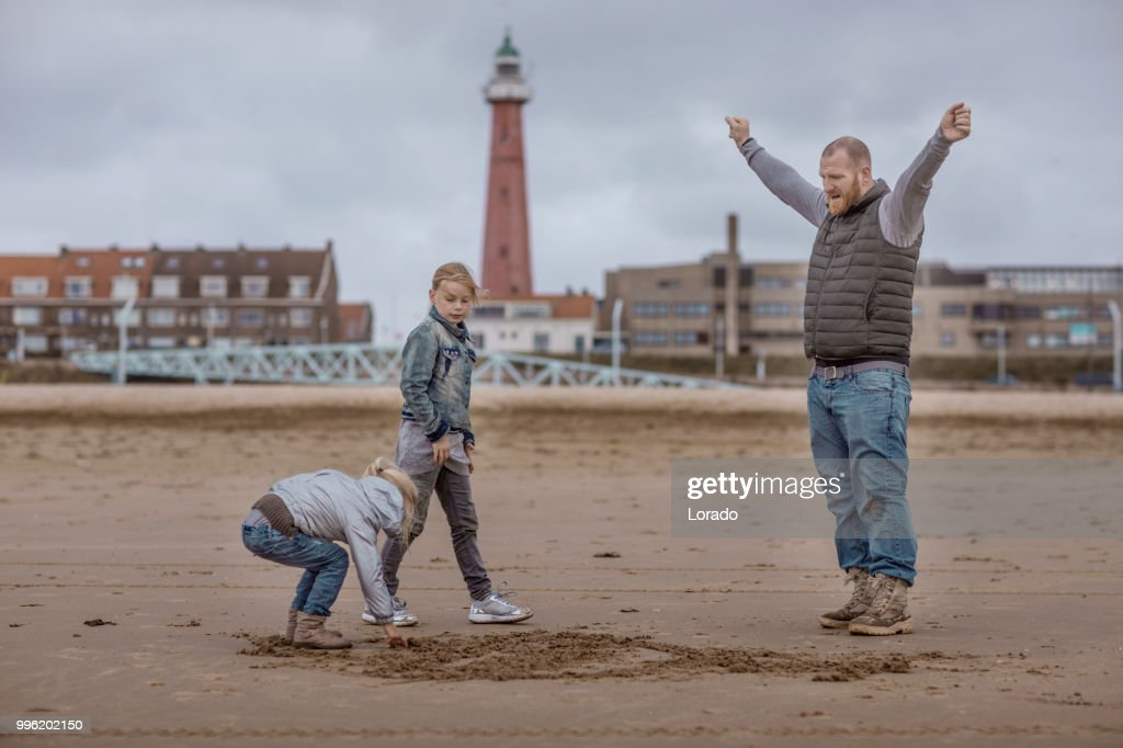 Single father and his daughters playing family games on a winter beach : Stock Photo