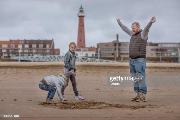 Single father and his daughters playing family games on a winter beach