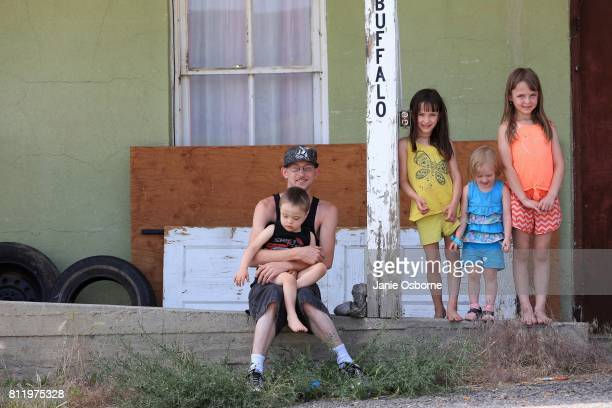 Single father and lifelong Butte resident Darren Drabant sits for a portrait in front of his Butte home with his four children Ayden Drabant Mattea...