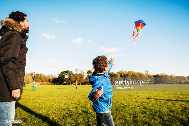 single father and son having fun flying kite - kite stock pictures, royalty-free photos & images