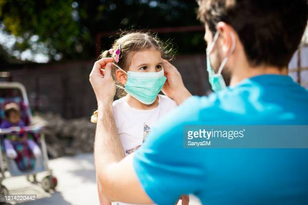 single father applying pollution mask to his daughter - protective face mask stock pictures, royalty-free photos & images