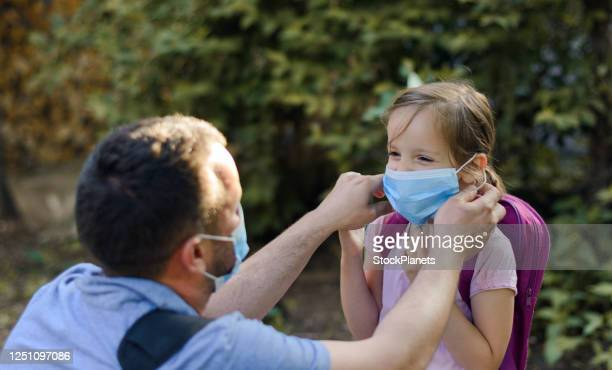 single father applying protective mask to his daughter - new normal concept stock pictures, royalty-free photos & images