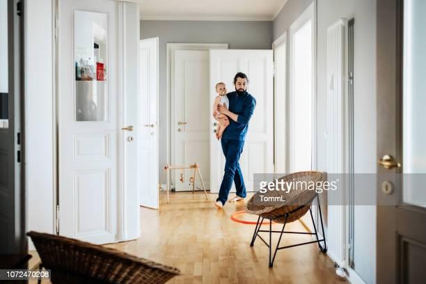 alleenstaande vader baby uitvoering door huis - gang stockfoto's en -beelden
