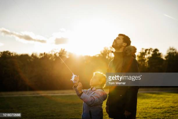 single father flying kite with his son - sonnenlicht stock-fotos und bilder