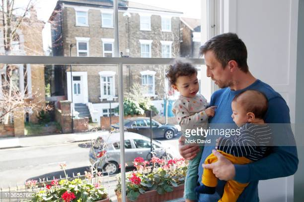 Single father holding baby son and daughter by window