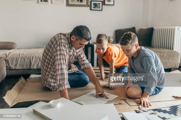 pai solteiro é montagem móveis com seus filhos. - instruções - fotografias e filmes do acervo