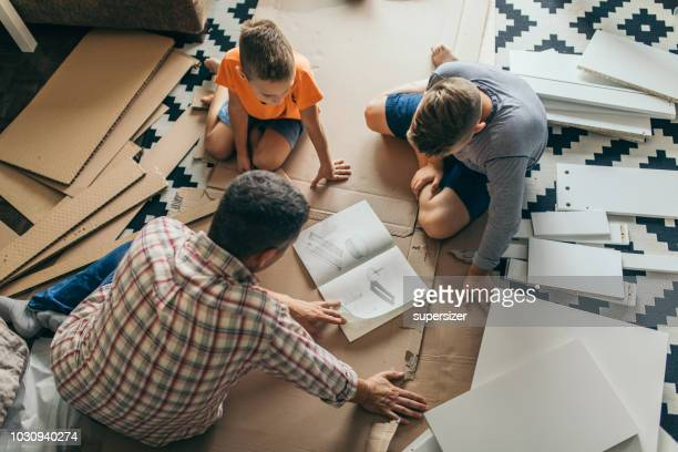 single father is assembling furniture with his kids - instruction manual stock photos and pictures