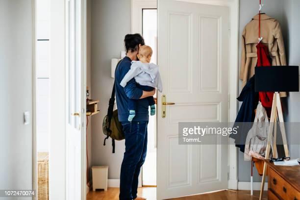 single father leaving house with his baby - leaving imagens e fotografias de stock