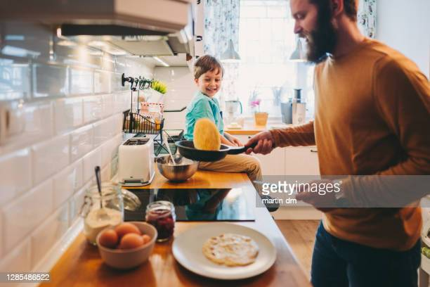 single father preparing pancakes during covid-19 lockdown - throwing stock pictures, royalty-free photos & images