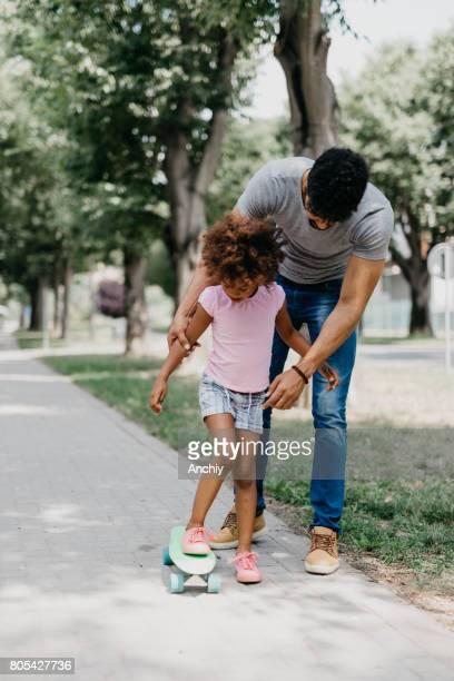 Père célibataire enseigne à sa fille comment monter une planche de penny