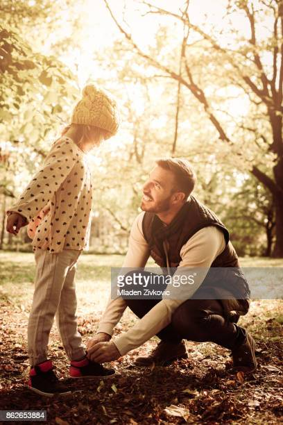 Single father tying his daughter shoes in park.