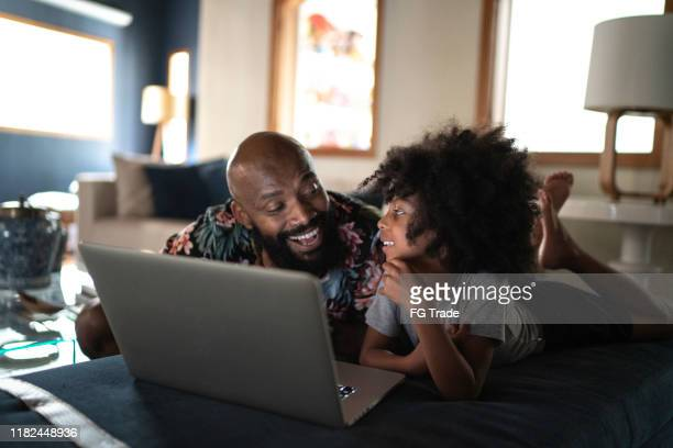 single father wacthing movie on a laptop with his daughter - mood stream stock pictures, royalty-free photos & images