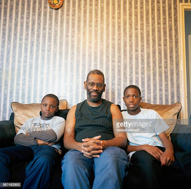 A single father with his nephews whom he has adopted in their flat on the Kingsmead Estate in Homerton in the eastern part of Hackney The estate has...