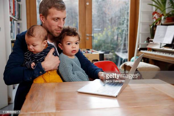 single father working from home with two children on lap - modern manhood stock pictures, royalty-free photos & images